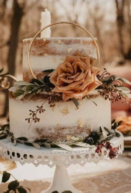 a naked fall backyard wedding cake with eucalyptus, a rust-colored rose and a gold ring plus dried blooms is chic