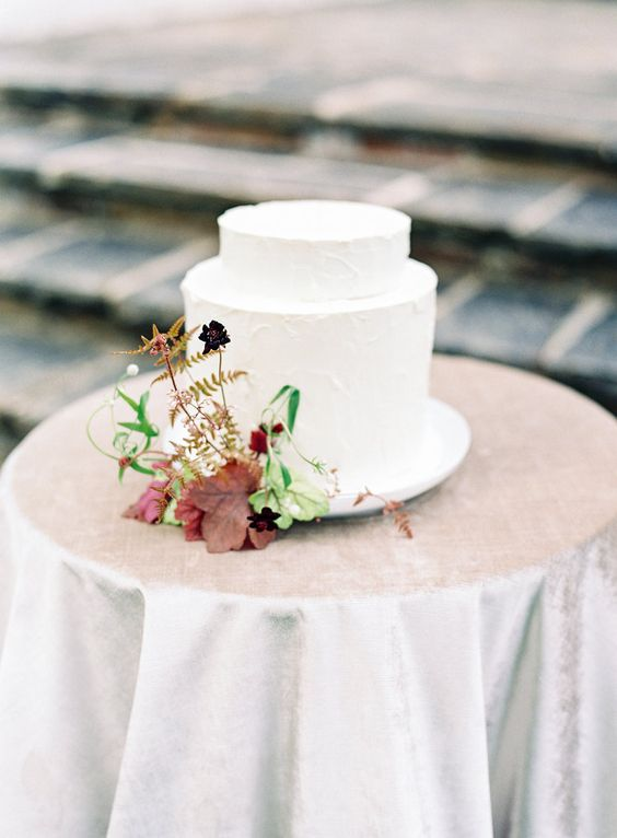 a refined modern fall wedding cake covered with white textural buttercream, with deep purple and burgundy blooms, greenery and dark leaves