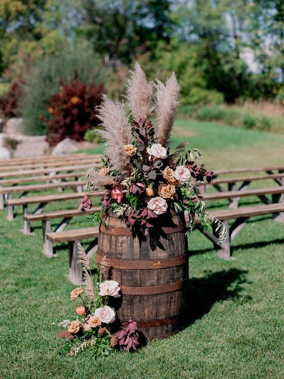 fall rustic and boho wedding floral arrangement with rust, blush and deep purple blooms and foliage, pampas grass on a barrel