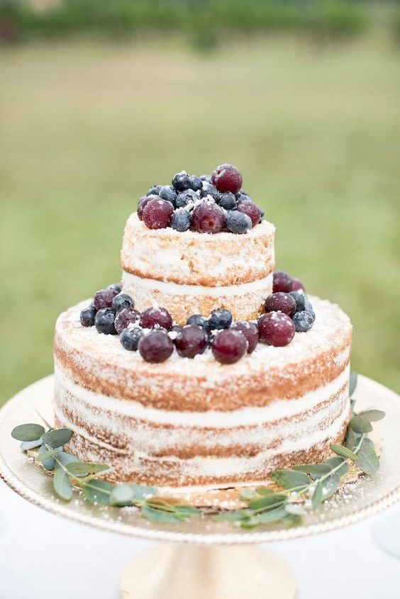 a naked wedding cake topped with fresh sugared berries is a lovely idea for a simple backyard wedding in the fall