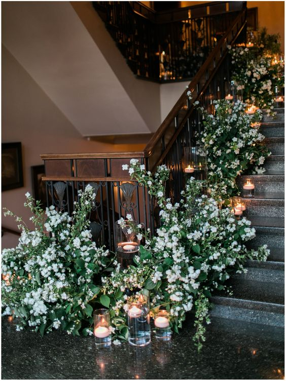 overgrown white blooms decorating a weddign staircase and floating candles to add even a cooler chic to the space