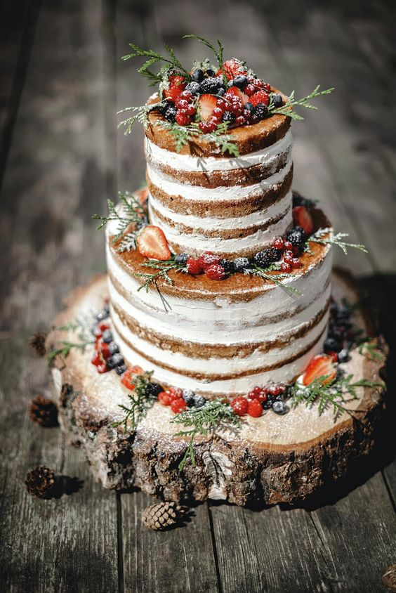 a naked wedding cake with greenery and fresh berries and sugar is a lovely idea for a backyard fall or winter wedding