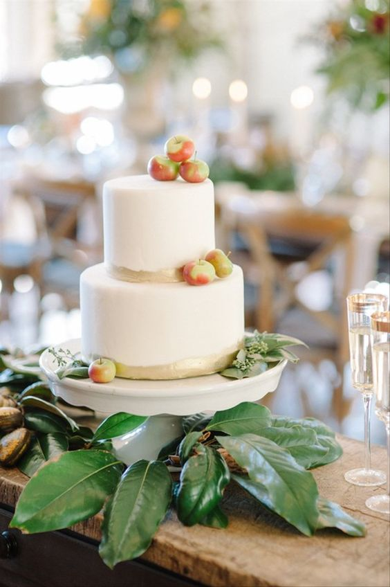 a simple modern fall wedding cake with gold touches and fresh apples and euclayptus is a very cool and beautiful idea