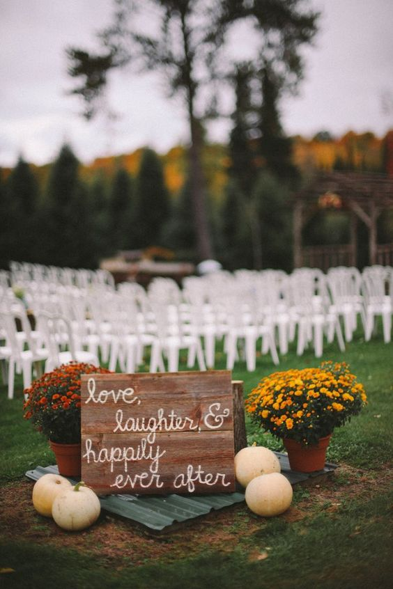 rustic fall wedding decor with a sign, pumpkins, bright potted blooms is a lovely idea for a rustic fall wedding ceremony space