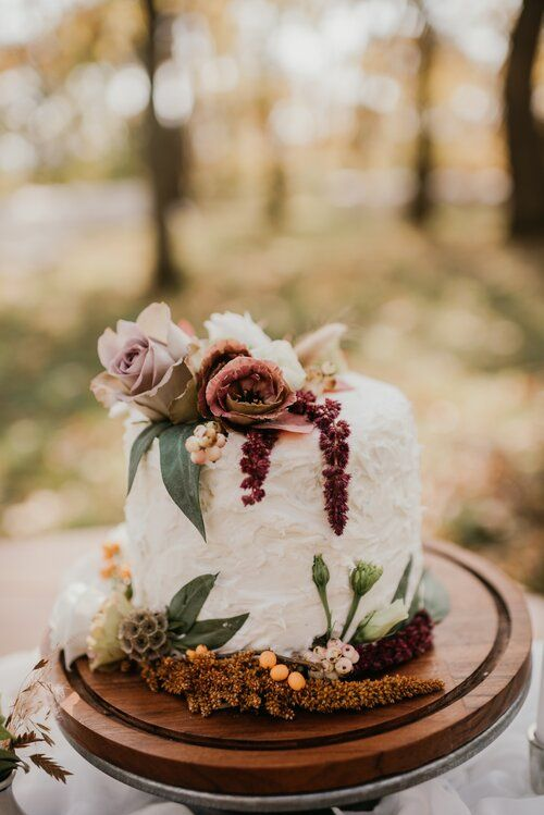 a simple and textural wedding cake with dusty pink and lilac blooms, greenery, berries and seed pods is a cool idea for the fall
