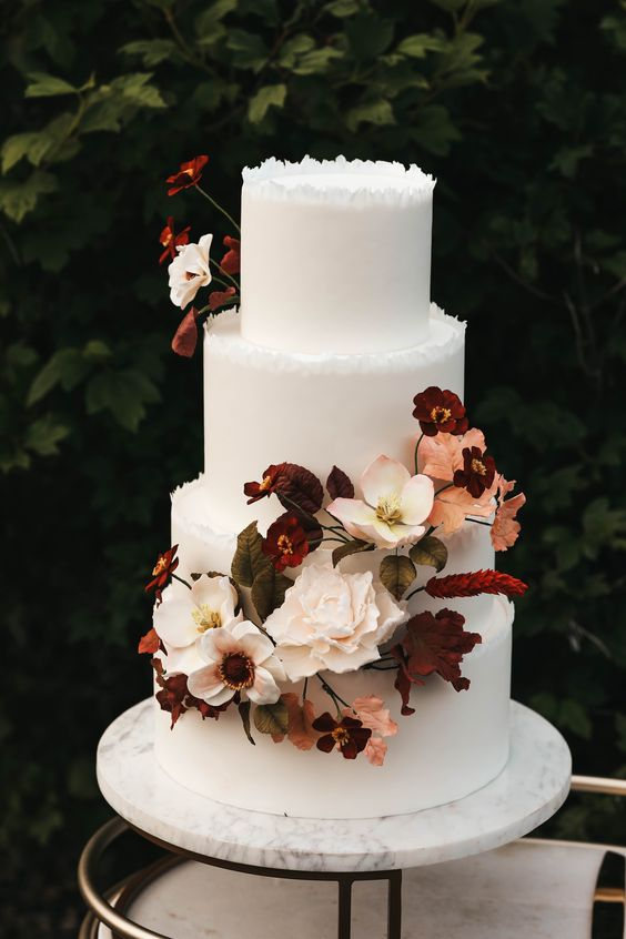 a sophisticated modern fall wedding cake with a rough edge, beautiful blush, burgundy blooms and bold foliage is amazing