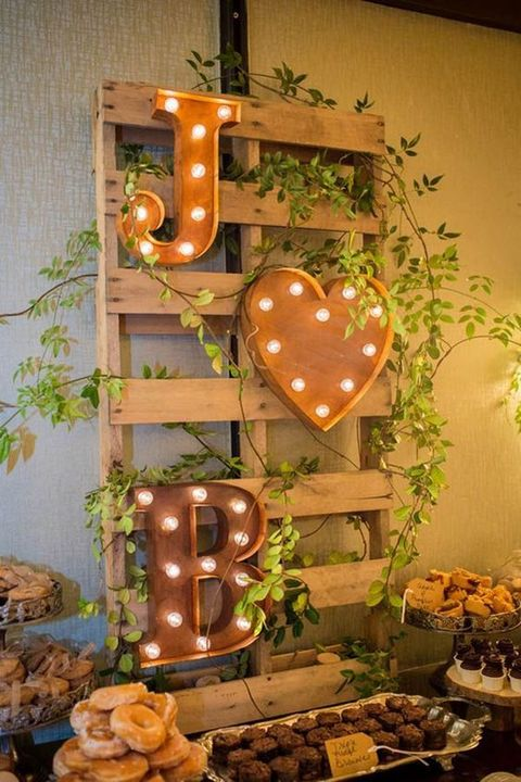rustic fall wedding decor of a pallet with marquee letters and a heart plus greenery climbing up is a cool idea