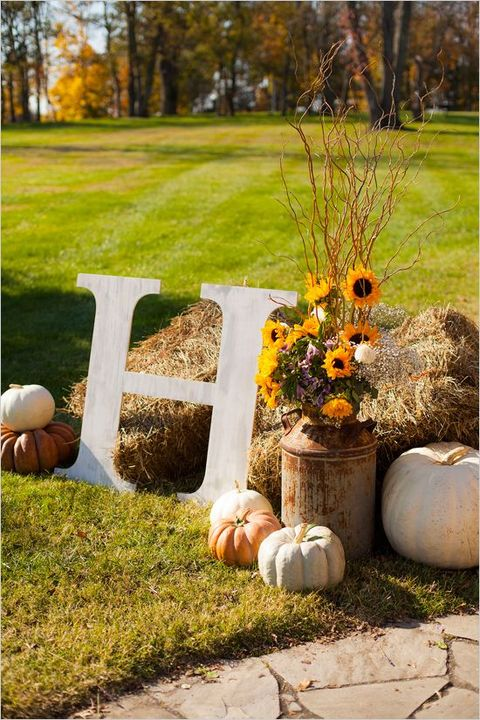hay with pumpkins, bold blooms, twigs and branches plus a monogram is a very cool and easy to realize idea for a fall wedding