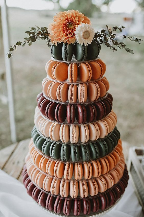 a cool alternative to a rustic fall wedding - a macaron tower in green, burgundy and orange, topped with bold blooms