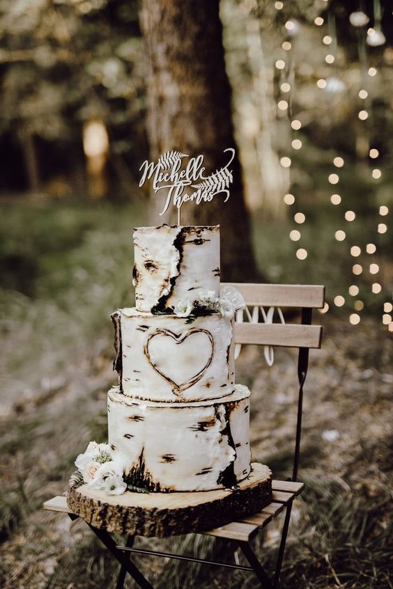a rustic fall wedding cake imitating birch bark with a heart cut out on it plus a calligraphy topper is super cool