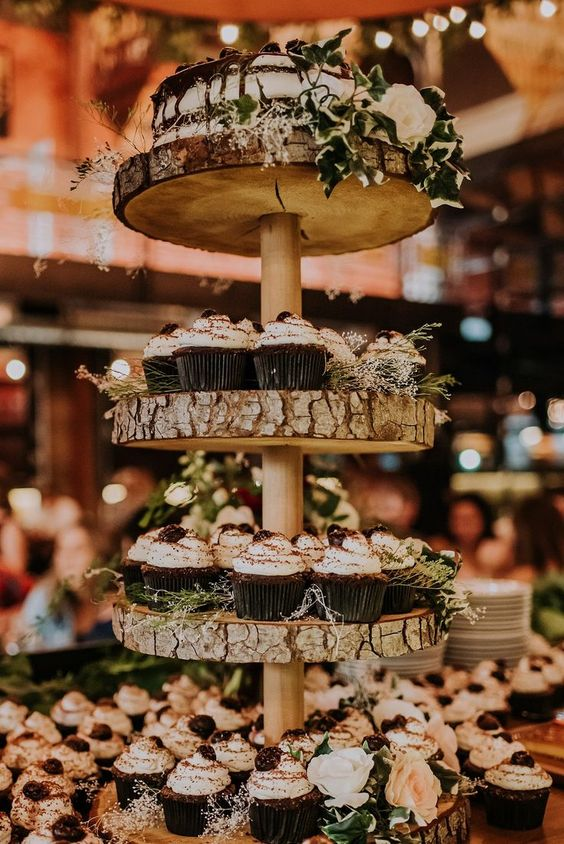 a wood slice stand with greenery and delicious cupcakes plus a naked wedding cake with chocolate drip on top