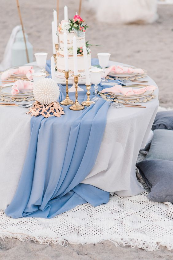 a beach wedding tablescape with a blue runner, pink napkins, a cake topped with pink blooms, driftwood and some elegant candles