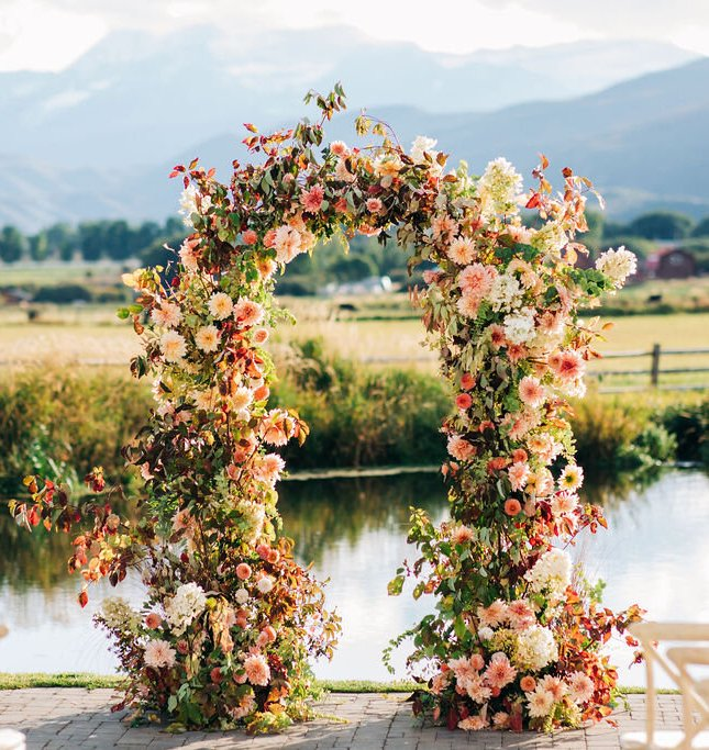 a beautiful and bright fall wedding arch of pink, blush and neutral blooms, greenery and bold foliage is a very cool and cheerful idea
