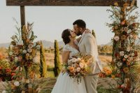 a beautiful and colorful rustic fall wedding arch lushly decorated with greenery, blush, rust, pink, orange and burgundy blooms, greenery and pampas grass