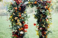 a beautiful and colorful rustic fall wedding arch with greenery, red, yellow, pink blooms, colorful fall leaves is a lovely idea for the season