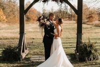 a beautiful and simple rustic fall wedding arch with pink, blush, burgundy blooms and greenery and fern arrangements at the base