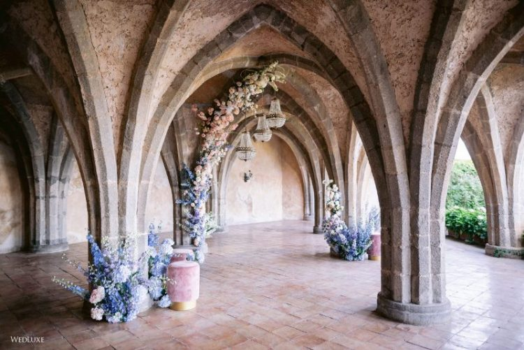 a beautiful castle wedding ceremony space with pink, blue and lilac blooms, pink stools and crystal chandeliers is amazing