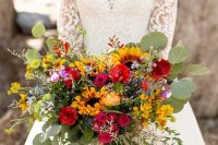 a beautiful colorful wedding bouquet with much textural greenery, red, pink and yellow blooms, sunflowers for a summer or summer to fall wedding