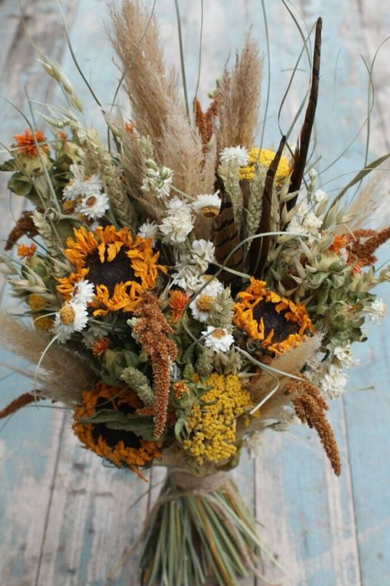 a beautiful dried flower wedding bouquet with pampas grass, sunflowers, astilbe, daisies, greenery for a fall or summer boho bride