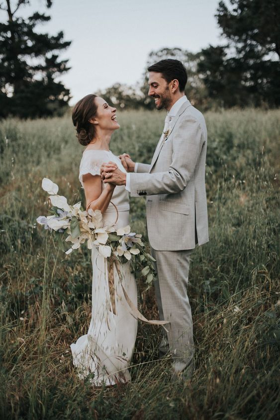 a beautiful hoop wedding bouquet with lush eucalyptus and lunaria plus shitles and ribbons is a very cute and chic idea