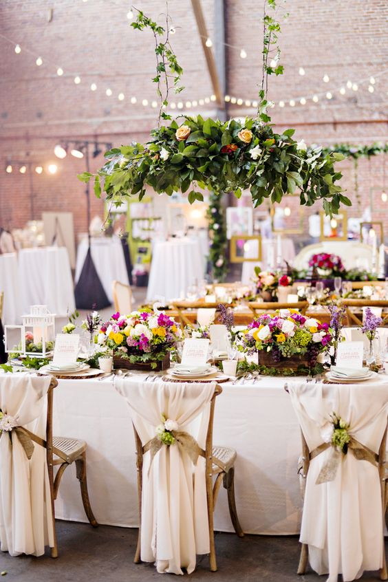 a beautiful indoor secret garden wedding tablescape with neutral linens and cool menus, with bold bloom centerpieces and an additional hanging one