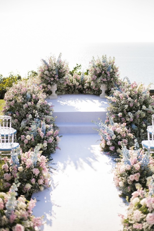 a beautiful pastel wedding ceremony space is amazing with pink, blue and white blooms and greenery is gorgeous
