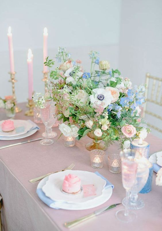 a beautiful pink and blue wedding table setting with a pink tablecloth, blue candles, pink tall candles, blue and pink blooms and pink desserts