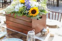 a beautiful rustic wedding centerpiece in a crate, with sunflowers, white hydrangeas, purple blooms, baby's breath and fern is a gorgeous solution