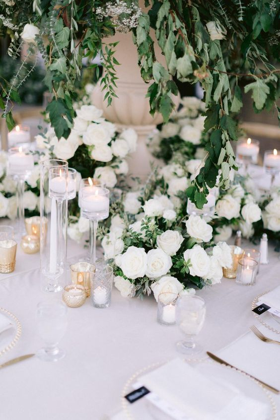 a beautiful secret garden wedding table setting in white, with roses, candles, elegant neutral linens and a lush greenery centerpiece