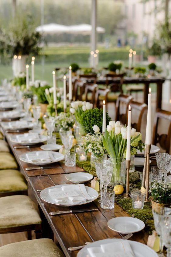 a beautiful secret garden wedding table with a moss runner, white blooms and greenery, lemons, tall candles and white plates