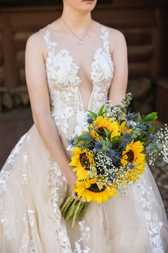 a beautiful wedding bouquet of sunflowers, baby's breath, thistles and greenery is a chic and bold idea for any summer bride