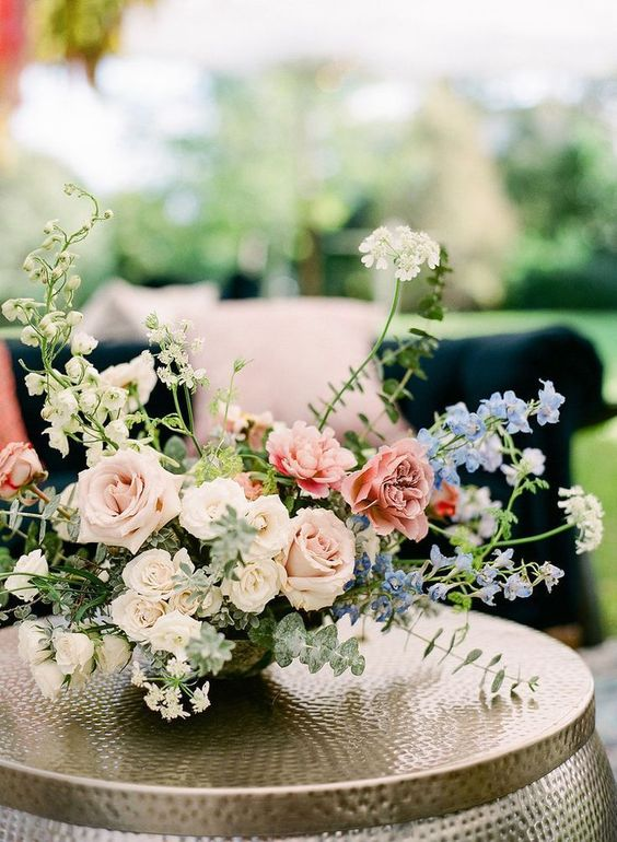 a beautiful wedding floral arrangement with pink, blue and white flowers and greenery is a gorgeous decoration or centerpiece