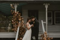 a boho fall wedding altar created right on the porch, with dried leaves, blooms and grasses is a very cool yet moody idea