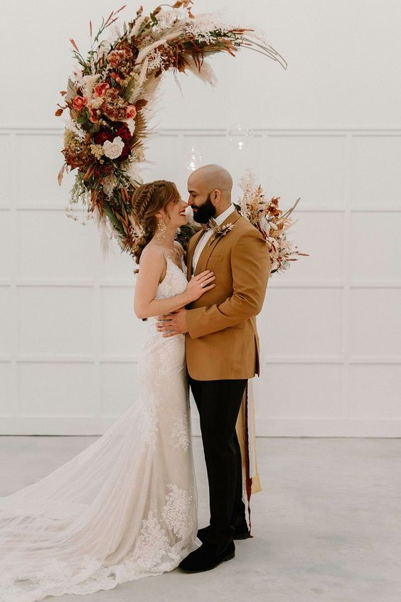 a boho fall wedding altar shaped as a crescent moon, with pink, burgundy, white blooms, greenery, pampas grass is wow