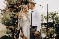 a boho fall wedding arch decorated on one side and at the base with greenery, pampas grass, feathers, bold and dark blooms