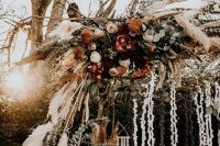 a boho fall wedding arch with greenery, blush, rust and burgundy blooms, pampas grass, tassels and garlands of petals is wow