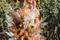 a boho fall wedding bouquet of sunflowers, dried and spray painted leaves, billy balls, colorful ribbons is a cool idea to rock