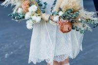 a boho hoop wedding bouquet with pampas grass, eucalyptus, white and brown dried blooms is a cool idea for a fall wedding