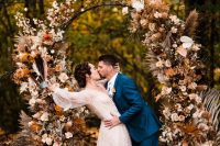 a boho lux fall wedding arch decorated with blush, rust-colored, peachy blooms, fronds, grasses, leaves and a baby's breath