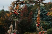 a boho rustic fall wedding arch with pampas grass, pink, blush, red and burgundy blooms, greenery and fall leaves plus candle lanterns