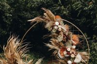a boho wedding backdrop with fronds, pampas grass, blush and white blooms and some greenery