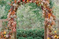 a bold and lush rustic fall wedding arch decorated with greenery, bold foliage, pink, red, mustard and yellow blooms and fruits