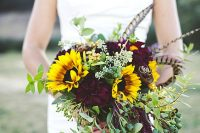 a bold and sumptuous wedding bouquet with lots of textural greenery, dark blooms, feathers and sunflowers is a cool idea for a fall boho bride