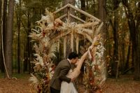 a bold boho fall wedding arch with pampas grass, bold dired fronds, greenery, colorful fall leaves and burgundy blooms inspires