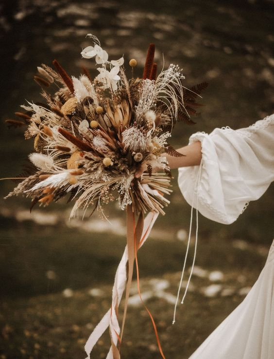a bold earthy tone dried wedding bouquet of billy balls, bunny tails, king proteas, ferns, lunaria and astilbe is ideal for a fall boho bride