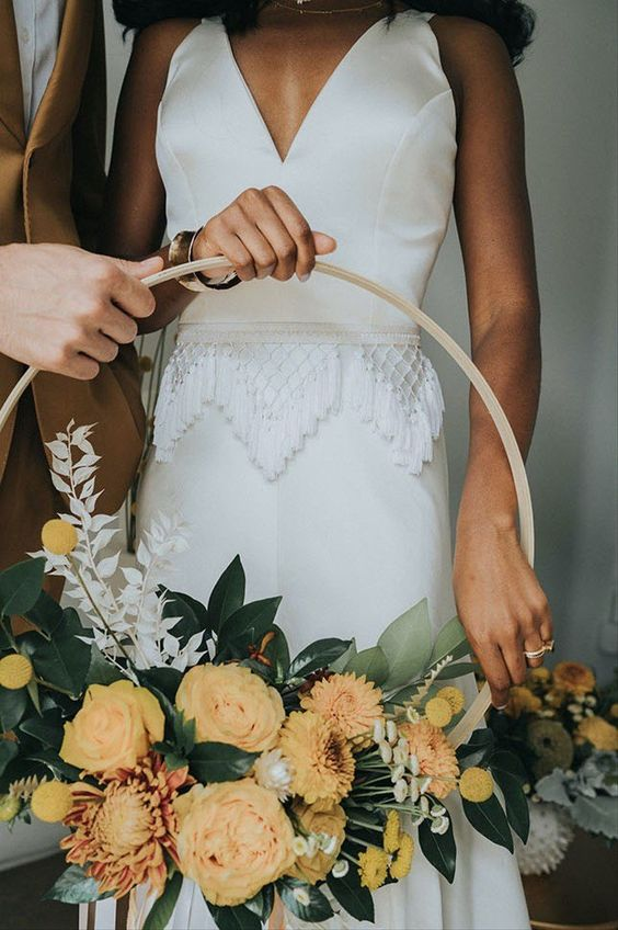 a bold fall hoop wedding bouquet with yellow blooms, billy balls, foliage and dried leaves is a lovely idea for the fall