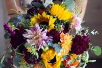 a bold fall wedding bouquet of sunflowers, pale pink, burgundy blooms, berries, eucalyptus and thistles is gorgeous
