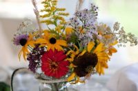 a bold floral wedding centerpiece of colorful blooms, sunflowers, lilac and yellow touches and dried grasses is amazing