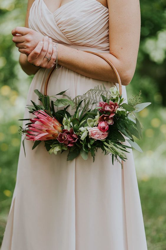 a bold hoop wedding bouquet with lots of greenery, pink blooms and a large king protea is a cool idea for a modern and romantic bride