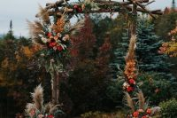 a bold rustic fall wedding arch composed of branches, pampas grass, greenery, blush, burgundy and red roses, candle lanterns and floral arrangements